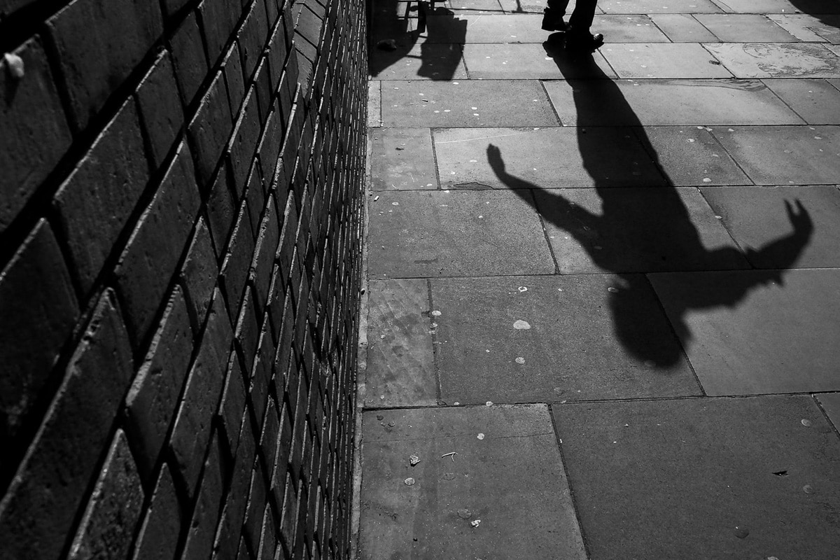 the shadow of a dancing man in the brick lane, london, photographed by Simon Hawkins Pictures