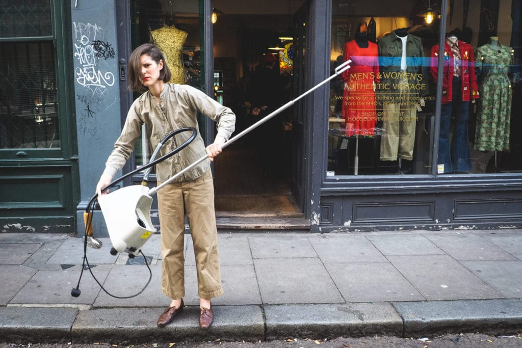 A lady empties water from her steam machine into the street in Brick Lane, London, photographed by Simon Hawkins Pictures