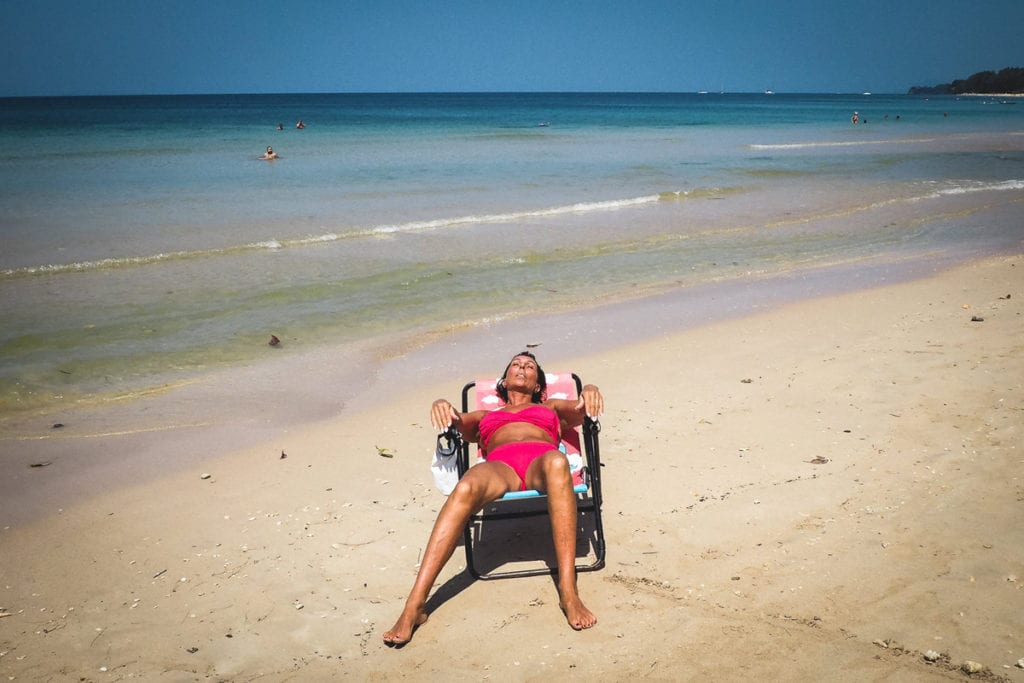 A lady in a oink bikini relaxes in a deck chair on a beach in thailand, photographed by street photographer Simon Hawkins Pictures