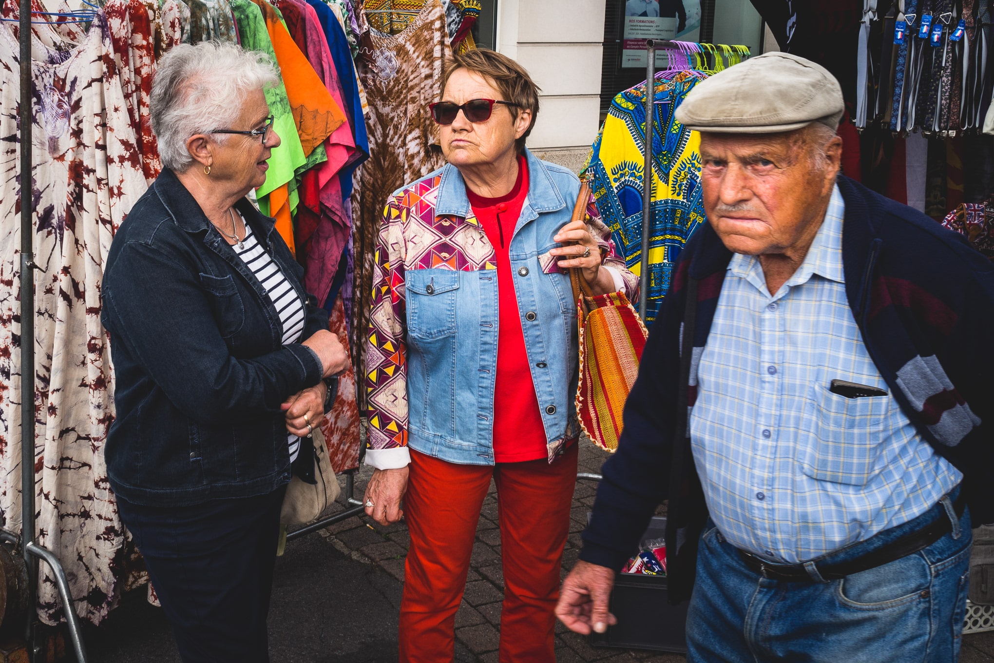 A man and two ladies at chateaubriant market in France photographed by documentary photographer Simon Hawkins