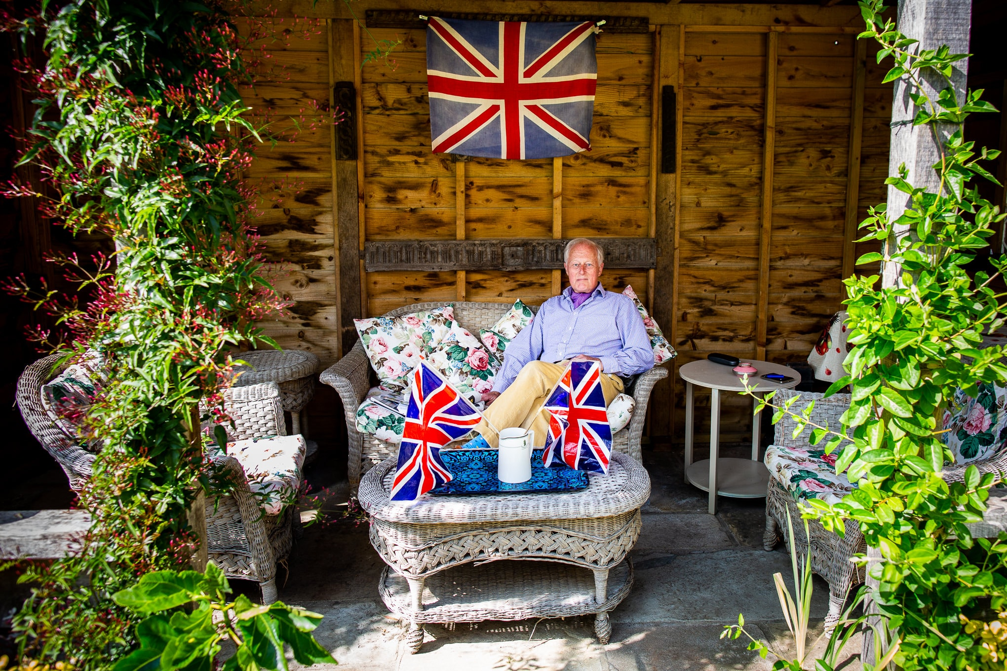 A man sits in garden in Faversham surrounded by union jack flags, photographed by documentary photographer Simon Hawkins