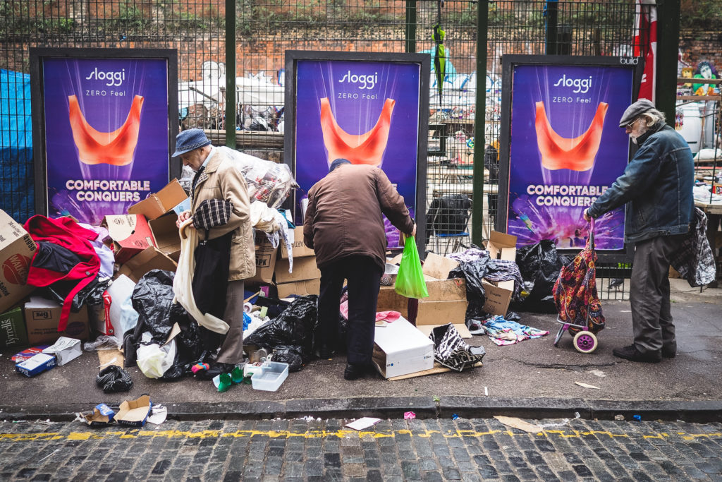 three men sort through jumble at a market in brick lane london, photographed by Simon Hawkins Pictures